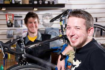 Smiling man in bicycle shop with others