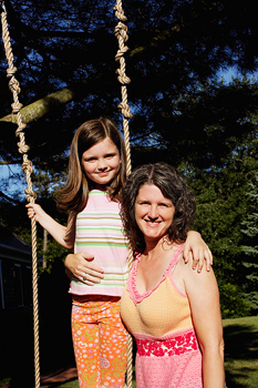 Mother posing with daughter on swing outdoors