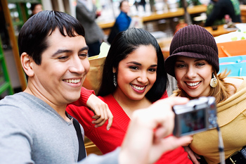 Three friends taking a photograph of themselves and smiling
