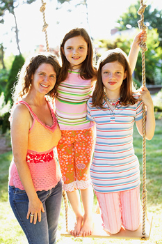 Mother posing with daughters on swing outdoors