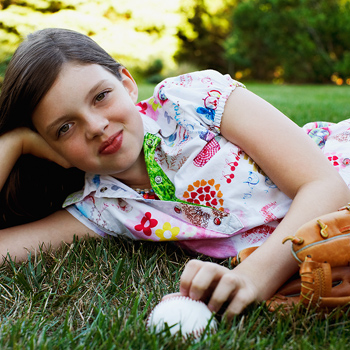Girl posing on lawn with baseball glove and ball