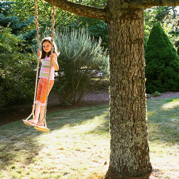 Girl standing on swing outdoors