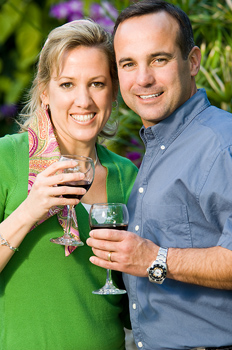 Smiling couple posing with wine