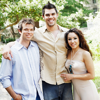 Two men and woman posing together outdoors