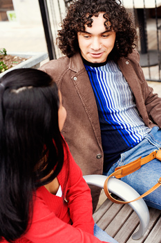 Couple sitting and talking on outdoors bench