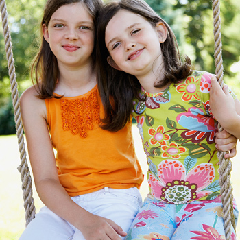 Sisters posing together on swing