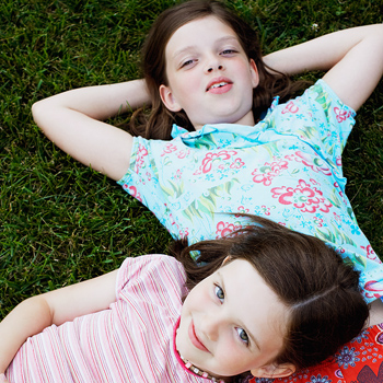 Girls relaxing together on lawn