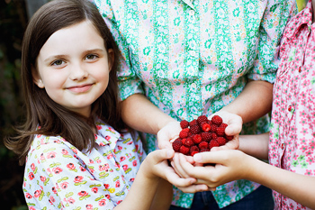Girl holding raspberries in cupped hands