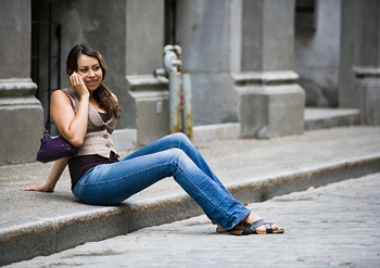 Woman smiling on cell phone on city curb