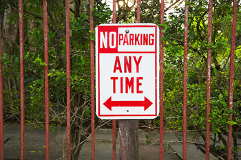 No parking sign on wrought iron fence