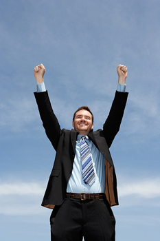 Smiling businessman cheering with arms raised