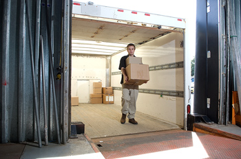 Man unloading boxes from truck into warehouse