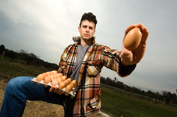 Man posing outdoors holding egg