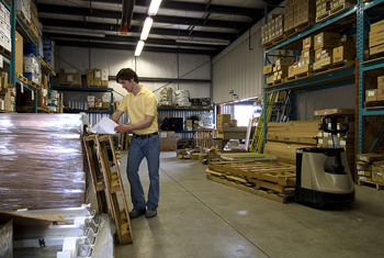 Man consulting paperwork in warehouse