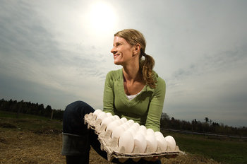 Kneeling woman holding tray of fresh eggs