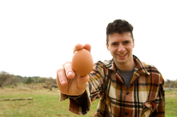 Smiling man posing fresh egg outdoors