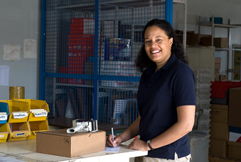 Smiling woman posing at shipping desk in warehouse