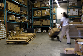 Woman pushing hand truck in warehouse