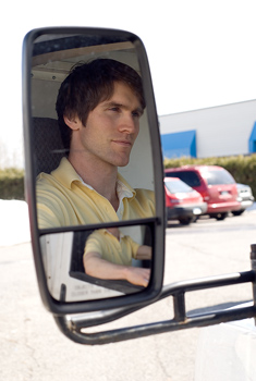 Reflection of man in rear view mirror of truck