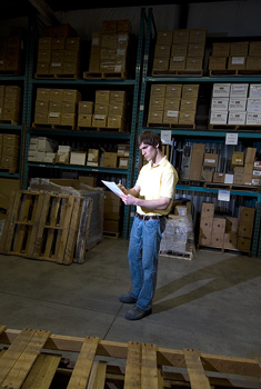Man standing in warehouse reading document
