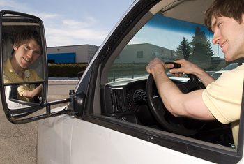 Man admiring himself in rear view mirror of truck