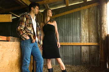 Couple posing in barn outdoors