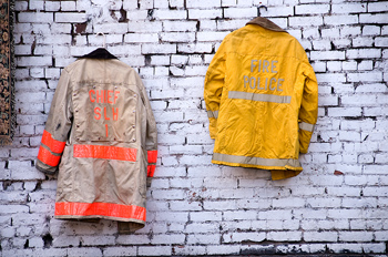 Fire and police coats hanging on brick wall