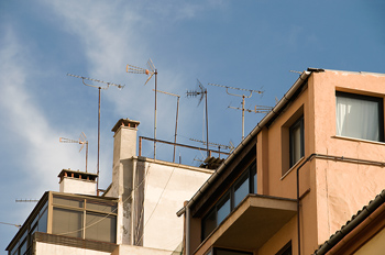 Chimneys and antennae on roof of building in Spain