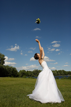 Bride outdoors in park tossing bouquet