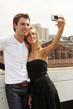 Young adult couple taking self-portrait with camera in urban outdoors