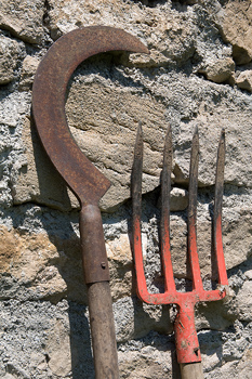 Sickle and pitchfork leaning against stone masonry wall
