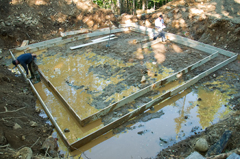 Two construction workers building frame for foundation at site in forest