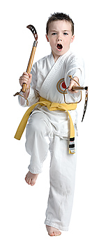 Boy in martial arts action pose with weapons