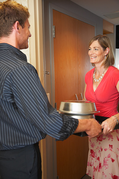 Man delivering hotel room service to woman