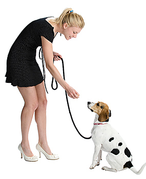 Blonde woman offering treat to puppy on leash