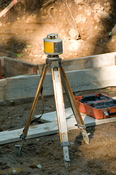 Rotary laser locator atop tripod at construction site