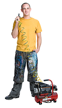 Man posing with paint sprayer and air compressor
