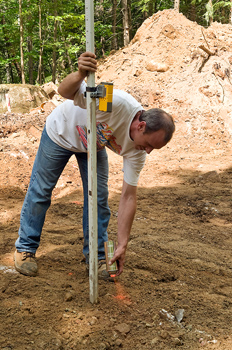 Man with prism pole marking soil at construction site with spray paint
