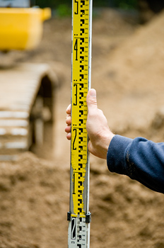 Hand holding prism pole at construction site