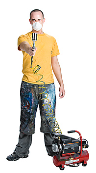 Man in filter mask aiming nozzle of paint sprayer