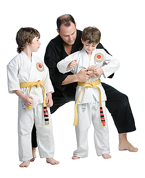 Martial arts instructor teaching two boy students