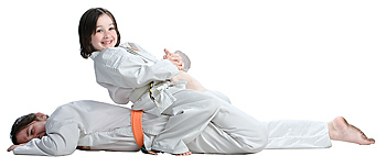Girl sitting atop another girl in martial arts combat