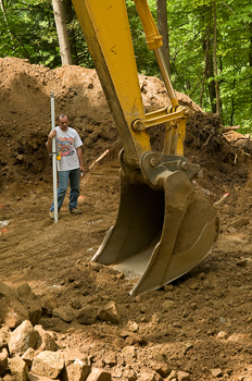 Man holding leveling rod and excavator scooping soil