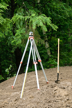 Theodolite on tripod with shovel at construction site
