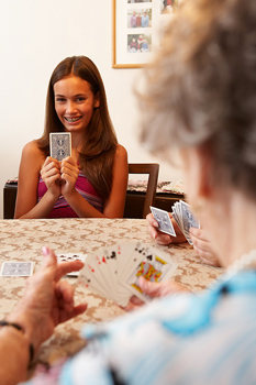 Smiling girl playing cards with others