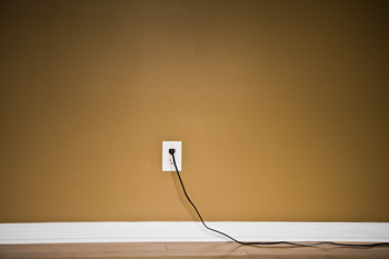 Electrical cord plugged into wall outlet