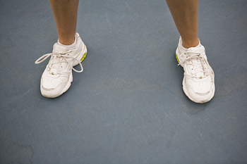 Sneakers on feet of woman tennis player