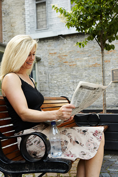 Businesswoman on bench outdoors reading newspaper