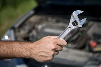 Car breakdown and hand of man gripping wrench