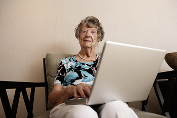 Elderly woman in chair with laptop computer